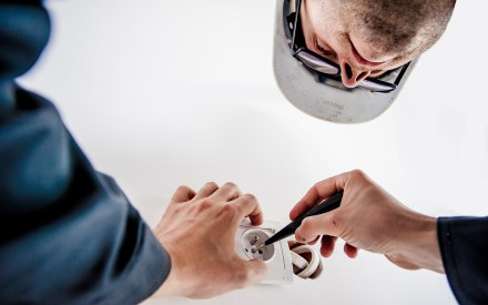 male electrician using a screwdriver to work on a 3 point plug
