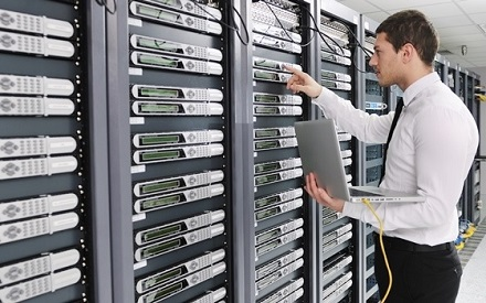 male facilities manager plugging cables into data centre server
