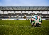 adidas football on grass field in empty sports stadia