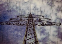 looking upwards at power transmission lines with blue skies and cloudy backdrop