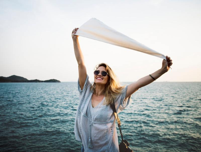 happy woman holding white scarf ocean