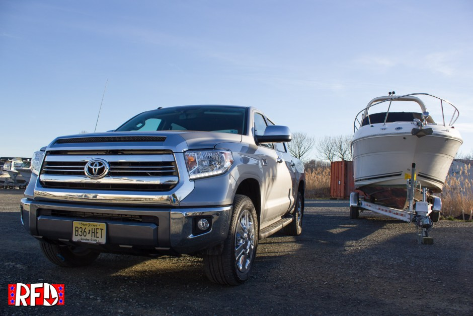 Silver 2017 Toyota Tundra 1794 Edition next to a boat on a trailer.