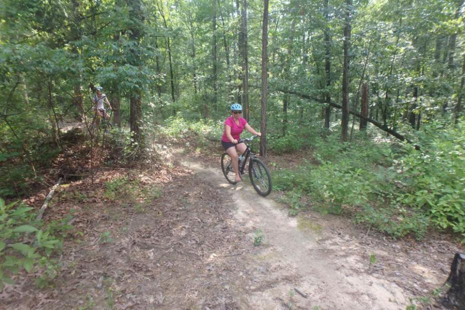 A mountain biker makes her way down the trail on a shared use trail