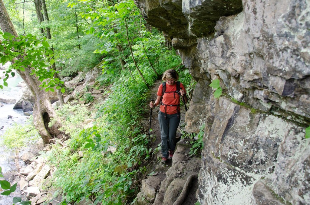 A hiker makes her way across a ledgy spot on her way to Twin Falls in the Richland Creek Wilderness Area