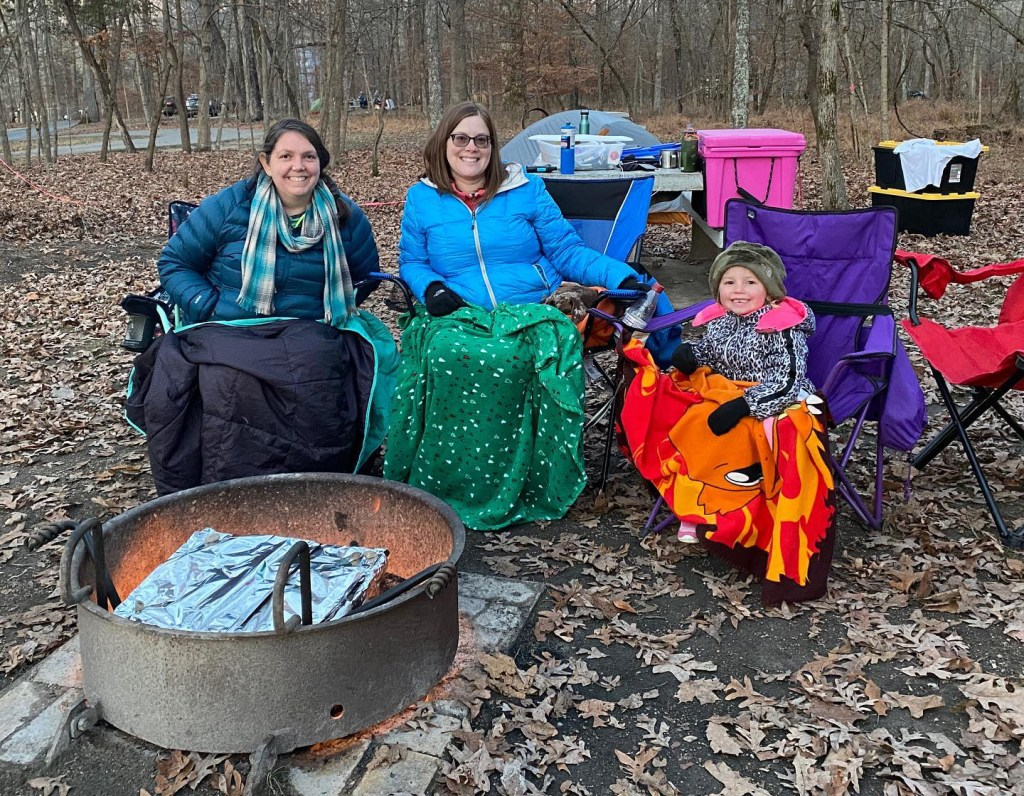 Two women and a child bundle up by the campfire