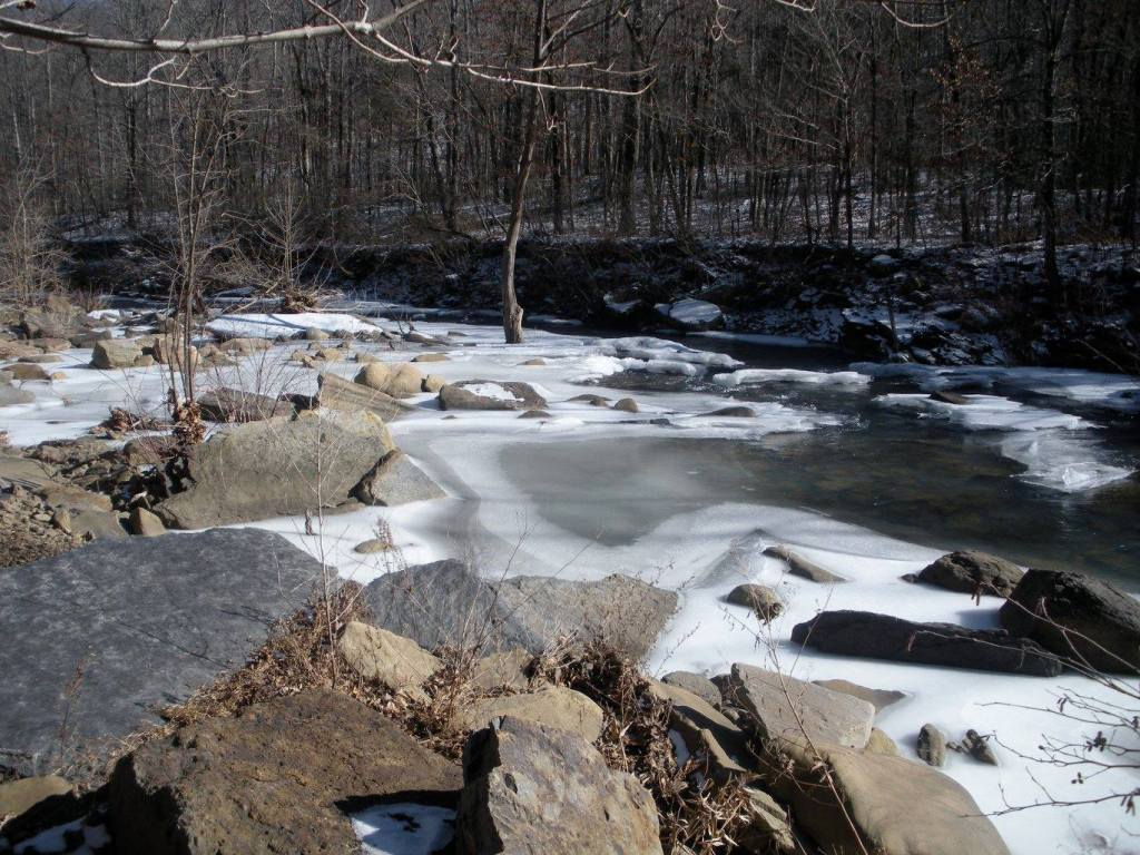 A frozen creek is shown on a cold weather camping trip