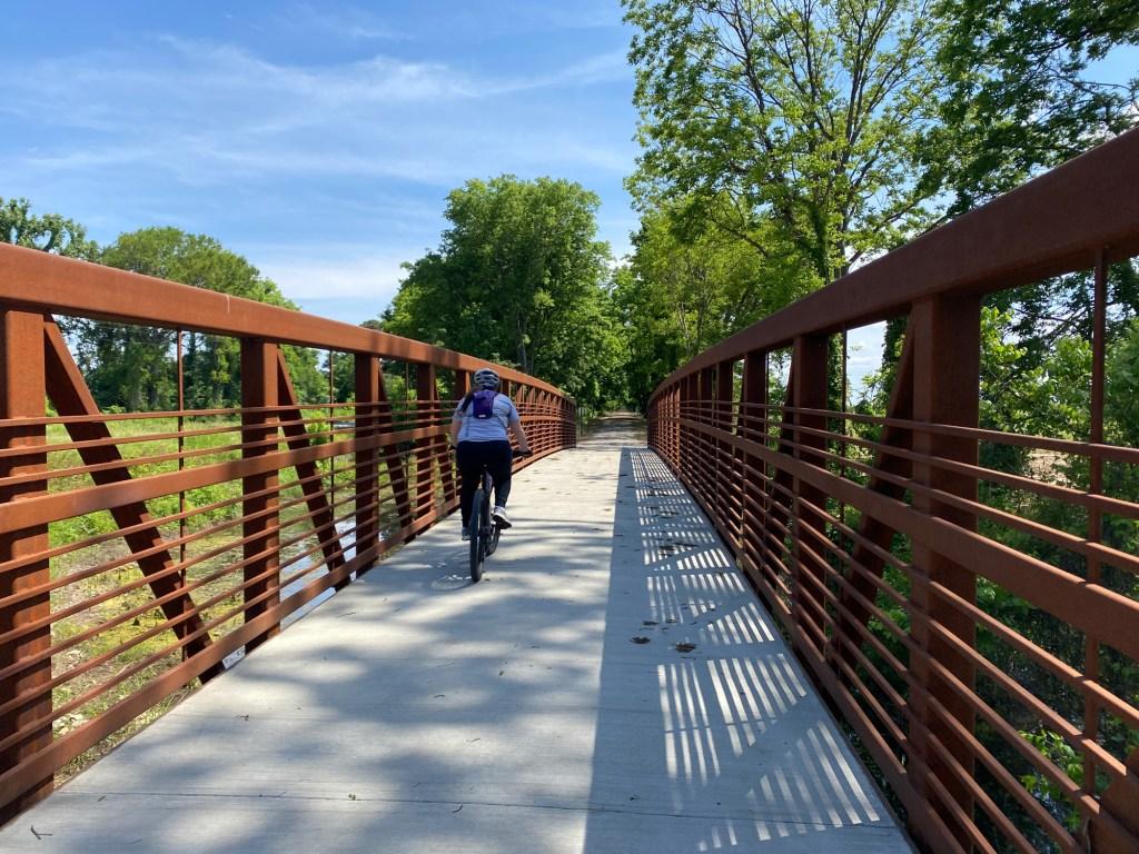A woman rides along a bridge