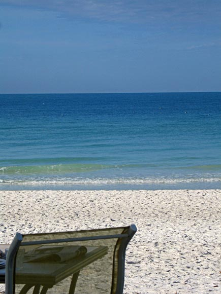 sling chair on white sand beach, anna maria island, florida