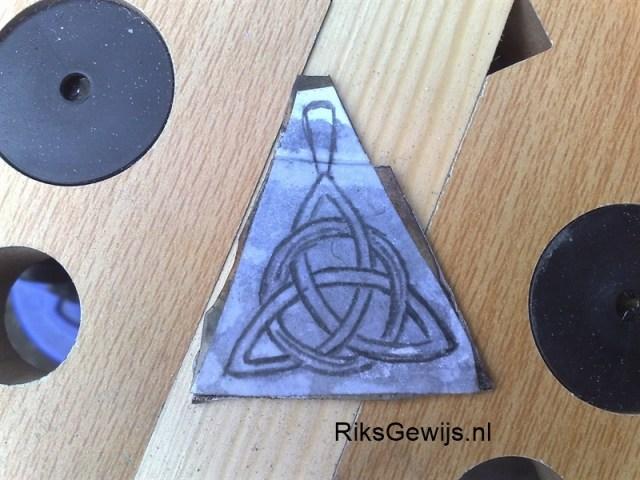 Het uitzagen van het driehoekje. Ik heb met een passer de hanger uitgezet en daarvan een schets gemaakt. Deze schets overgetrokken en op een uitgeknipt. Doordat ik dit dan op het metaal lijm is het makkelijk uit te zagen. Als materiaal heb ik Alpeca gekozen. Dit omdat dit zich gedraagt zoals zilver en ik dit op voorraad heb.