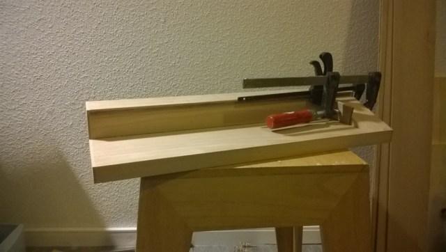 De basis is eigenlijk heel simpel. Plankje en een blokje er op vast gelijmd. In het blokje worden gaatjes geboord waar de gereedschappen in kunnen staan. Als eerst het blokje gelijmd en dit met fineer afgewerkt.