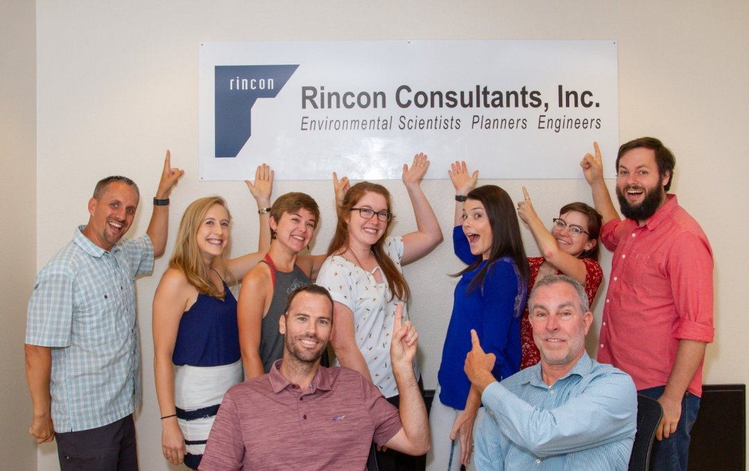 Group of people smiling and pointing to Rincon Consultants sign in Sacramento.