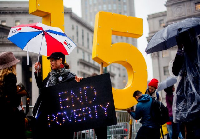 Supporters of a $15 minimum wage at a gathering in November in Manhattan. A group of liberal and conservative economists produced a plan on alleviating poverty. Credit Sam Hodgson for The New York Times