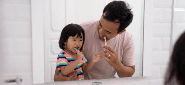 Dad and kid brushing teeth