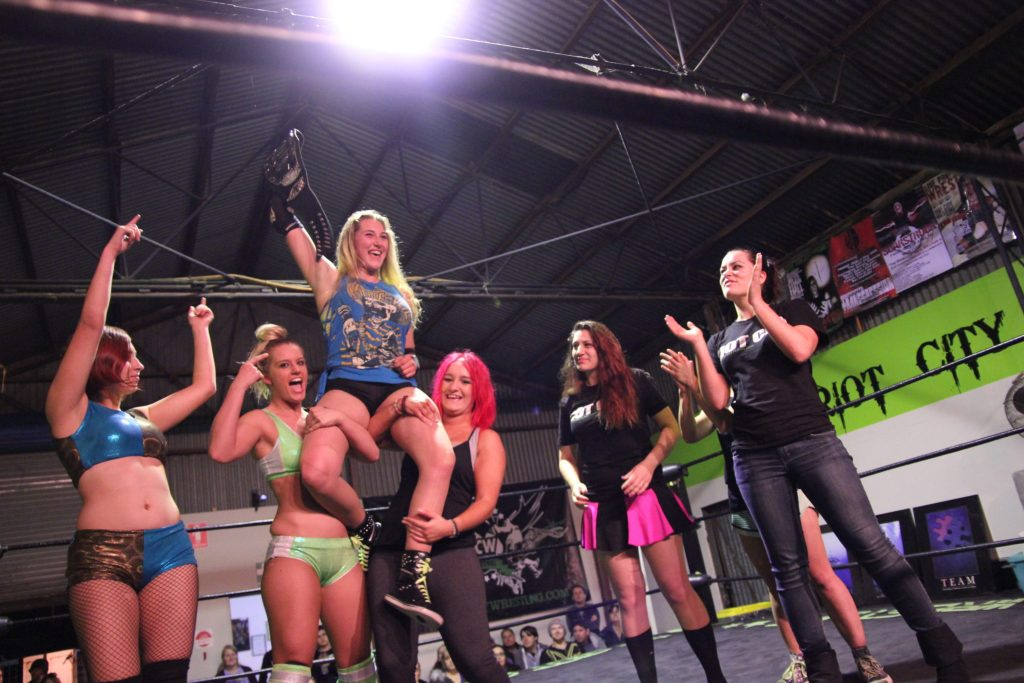 Demi Bennett holding the womens' title high while sorrounded by female wrestlers