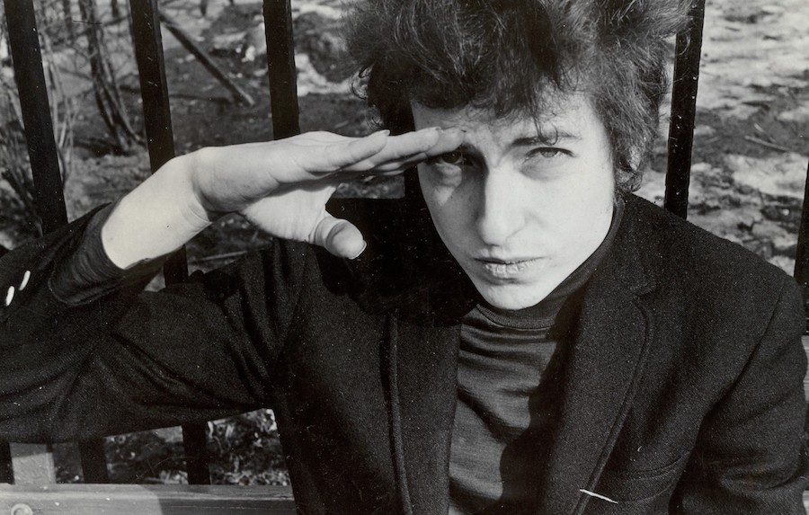 Fred W. McDarrah: Bob Dylan, sitting on a bench in Christopher Park (across the street from the offices of the Village Voice since 1960), either salutes or shields his eyes from the sun, January 22, 1965