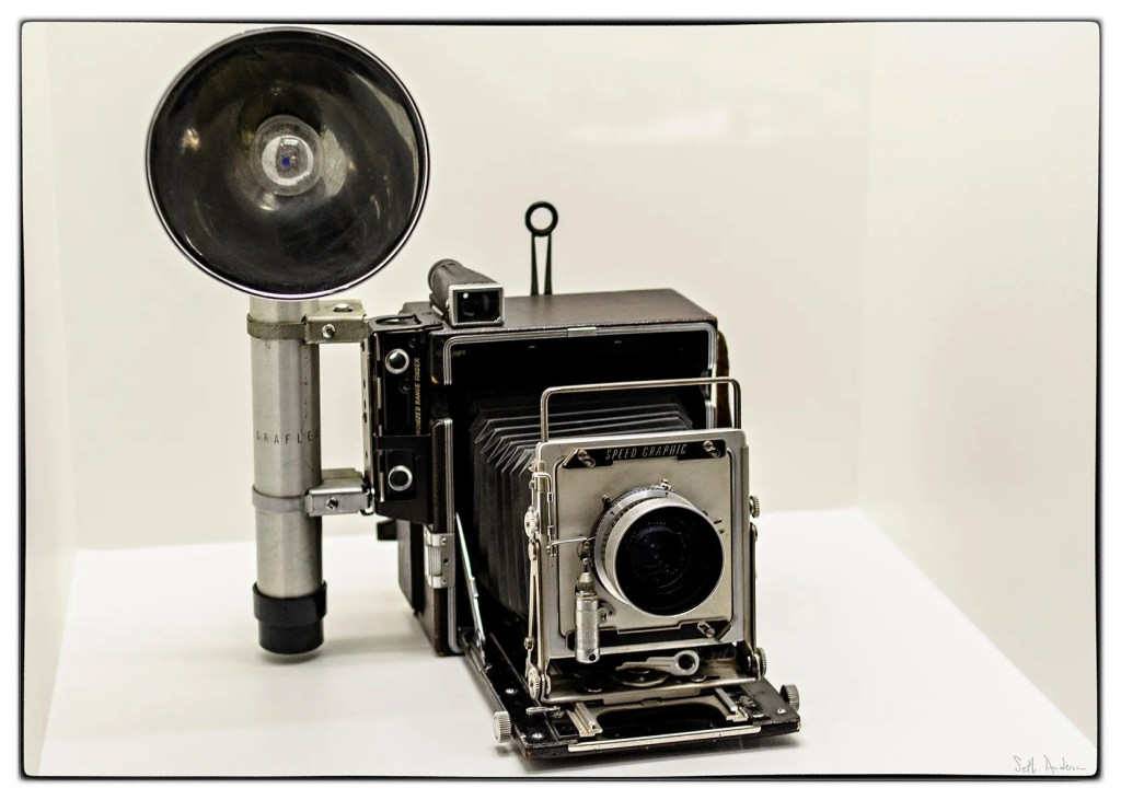 (Example of a Graflex camera with flash gun. This Graflex is Stanley Kubrick's Speed Graphic camera at the LACMA exhibit. Photo Credit: Seth Anderson via Flickr/Creative Commons)