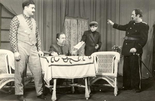 """Miu Ursulescu despre Teatrul Popular  Românesc din Vârșeț """"Fotografia reprezintă o scenă din spectacolul cu piesa """"O noapte furtunoasă"""" de I.L. Caragiale. Ansamblul, deși era destul de numeros, se muncea paralel la mai multe spectacole. Din acet motiv se mai angajau în unele dintre acestea și vreun amator. În fotografie îi vedeți pe: Eftimiu Ursulescu (la stânga – profesionist), Gheorghe Andraș – amator, Mircea Popi (băiatul Spiridon – amator) și Ion Petrică – profesionist."""""""