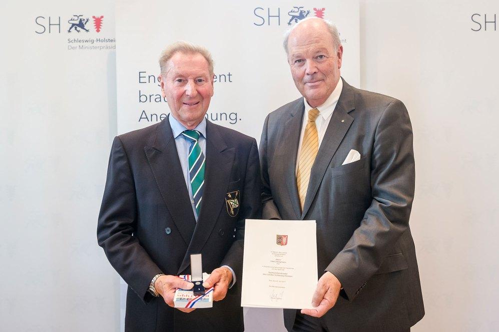 Innenminister Hans-Joachim Grote (r.) überreicht die Sportverdienstnadel an Uwe Zwingmann. Foto: Frank Peter