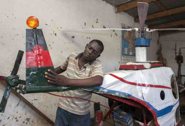 Felix Kambwiri inspects the helicopter he built in his garage. Credit: AFP / AMOS GUMULIRA