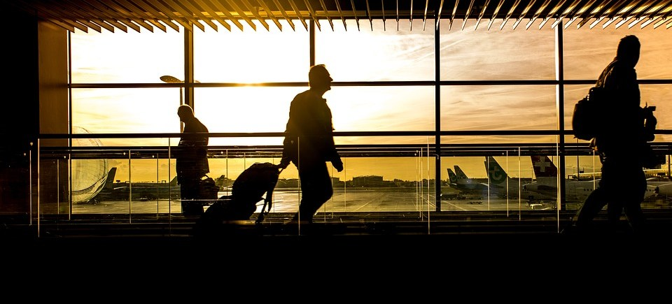 sunrise, silohuette, airport, man with suitcase, aeroplane tails in the background, man walking