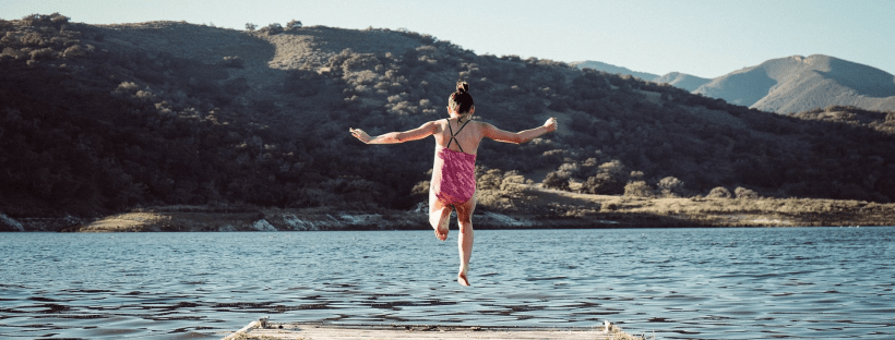 Girl in bathing suit, leaping off a wooden bridge into water