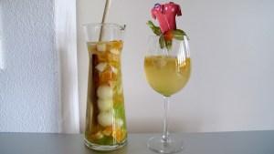 fertiger Sangria in Karaffe und in Weinglas, dekoriert mit Physalis und Trikot-Fähnchen