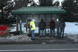 Suffolk County DPW workers clearing snow and ice from bus shelter on Route 58 yesterday. (RiverheadLOCAL photo by Peter Blasl)