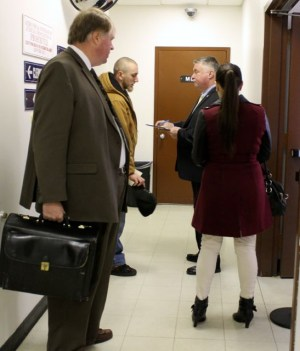 An attorney conferences with his client in the hallway outside the justice court clerk's office Monday. (RiverheadLOCAL photo by Denise Civiletti)