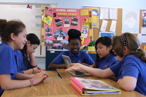 A group of sixth graders discuss possible solutions to make the road safer for students. Photo: Katie Blasl