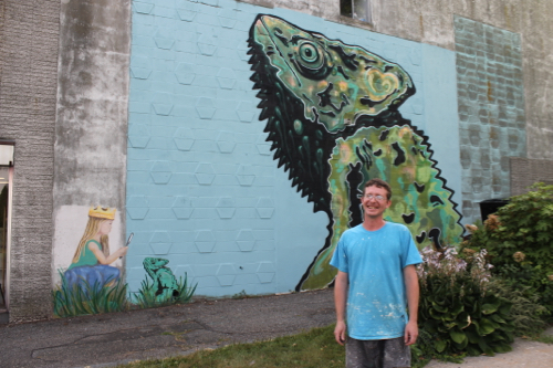 "Mural artist Drew Kane with his ""Chameleon"" on the wall of the East Main Street building next to First Congregational Church."