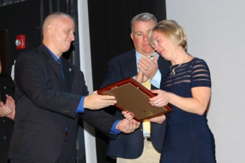 Tanya Newman, right, accepts an award from Riverhead PBA board member Rich Freeborn, as her husband Todd looks on. Photo: Peter Blasl