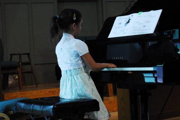 Girl standing and playing piano