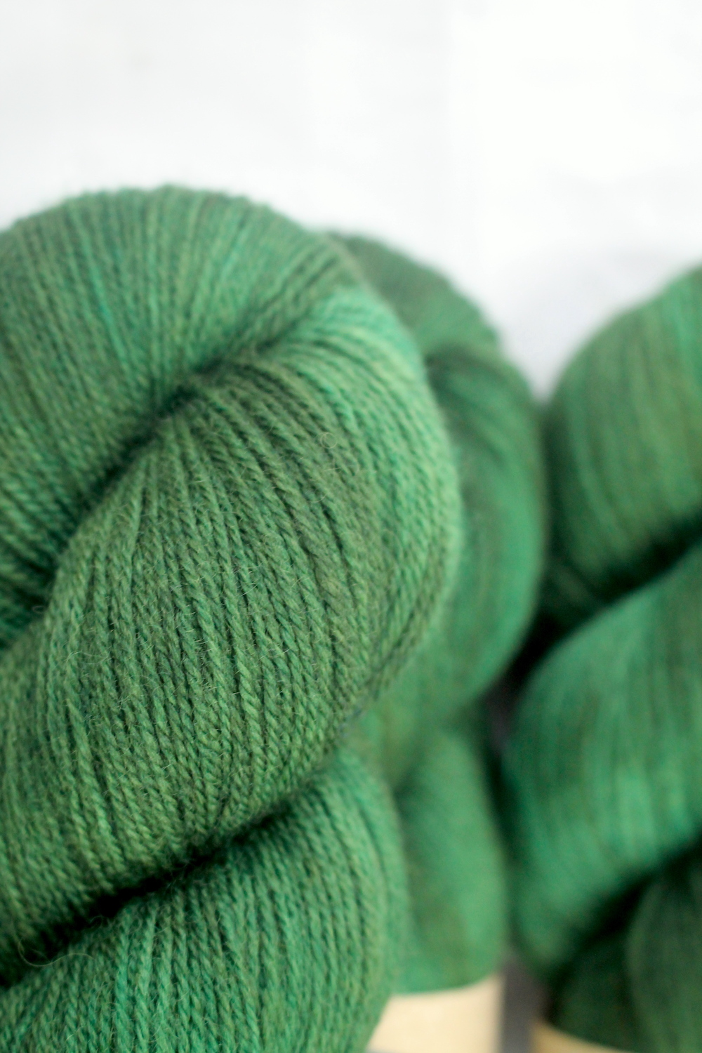 A pile of skeins of Nene 4 Ply in forest green