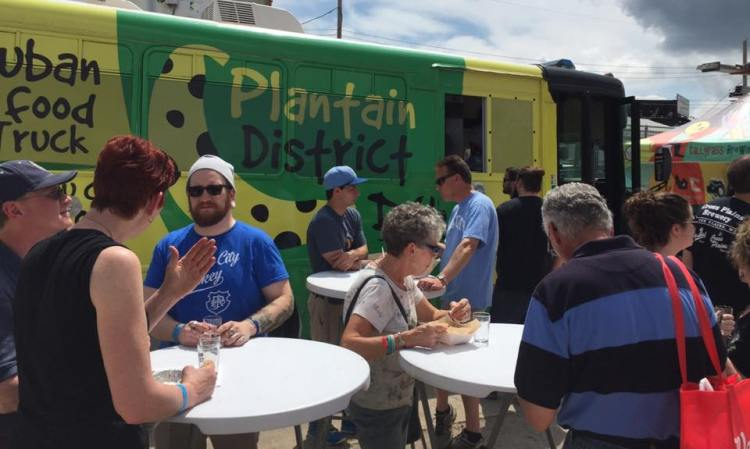 Patrons eating outside the Plantain District foodtruck in North Kansas City