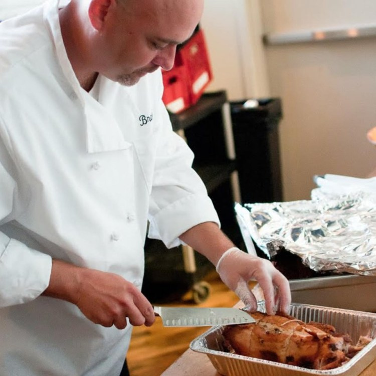 Chef Brad carves up pork for B-Rad's barbecue, smoked and braised meat-heavy menu.