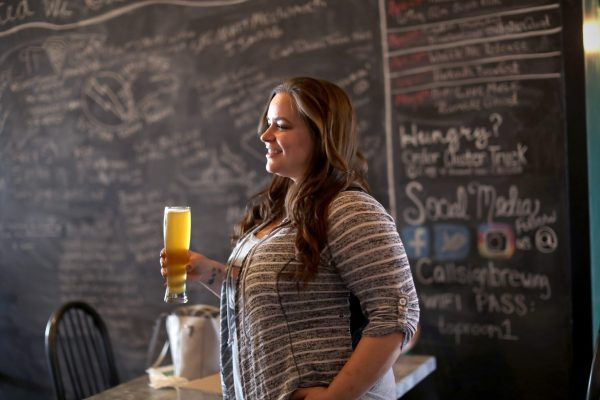 Woman holding craft beer outside Callsign Heroes Chalkboard