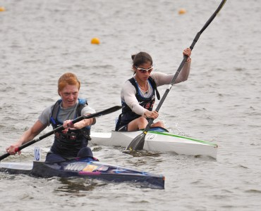 Image of Two female sprint kayakers racing on the Oklahoma River