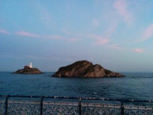"alt=""Photo from Mumbles Pier, Swanseas South Wales, of Knab Rock"""