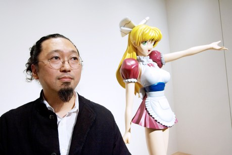 """Takashi Murakami, Japanese contemporary artist, poses with his work """"Miss ko2"""" sculpture at a gallery in Tokyo, Japan, on Friday, July 5, 2007. Murakami announced plans for his retrospective that will be held in Los Angeles, New York, Frankfurt and Bilbao. Photographer: Hitoshi Katanoda/Bloomberg News."""