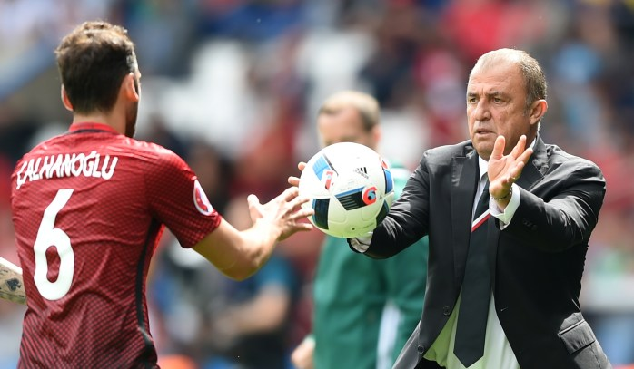 Turkey's coach Fatih Terim passes a ball to Turkey's midfielder Hakan Calhanoglu during the Euro 2016 group D football match between Turkey and Croatia at Parc des Princes in Paris on June 12, 2016. / AFP / BULENT KILIC (Photo credit should read BULENT KILIC/AFP/Getty Images)