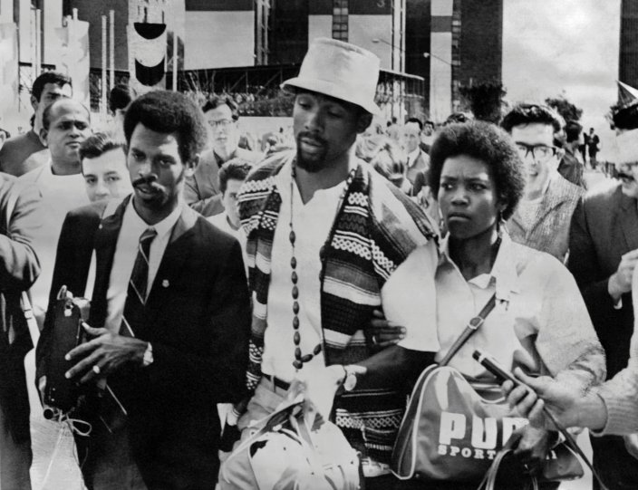 US sprinter John Carlos (C) leaves the Olympic village with his wife, after being suspended, along with his teammate Tommie Smith, from his national team and banned from the Olympic Village, because of the victory ceremony demonstration during the Mexico 1968 Olympic Games on October 18, 1968, in Mexico City. After having received their medals 17 October 1968 for first and third place in the 200 metres event, US athletes Tommie Smith and John Carlos raised their gloved fists in the Black Power salute to express their opposition to racism in the USA. / AFP / EPU / - (Photo credit should read -/AFP/Getty Images)