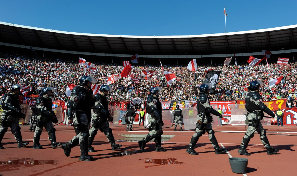 """Serbian anti riot police officers enter Belgrade's """"Marakana"""" stadium prior to the Serbian football derby match on October 23, 2010. Heavy police presence and strict fans' control prevented feared violence at the tense Serbian derby today won by Partizan against its main local rival Red Star Belgrade. Several thousands policemen were engaged since early morning hours, controlling groups of fans coming to the match in a clear bid to avoid any incidents following violent riots by Serbian hooligans on October 12 in aborted Serbia's Euro 2012 qualifier against Italy in Genoa. AFP PHOTO / Andrej ISAKOVIC (Photo credit should read ANDREJ ISAKOVIC/AFP/Getty Images)"""