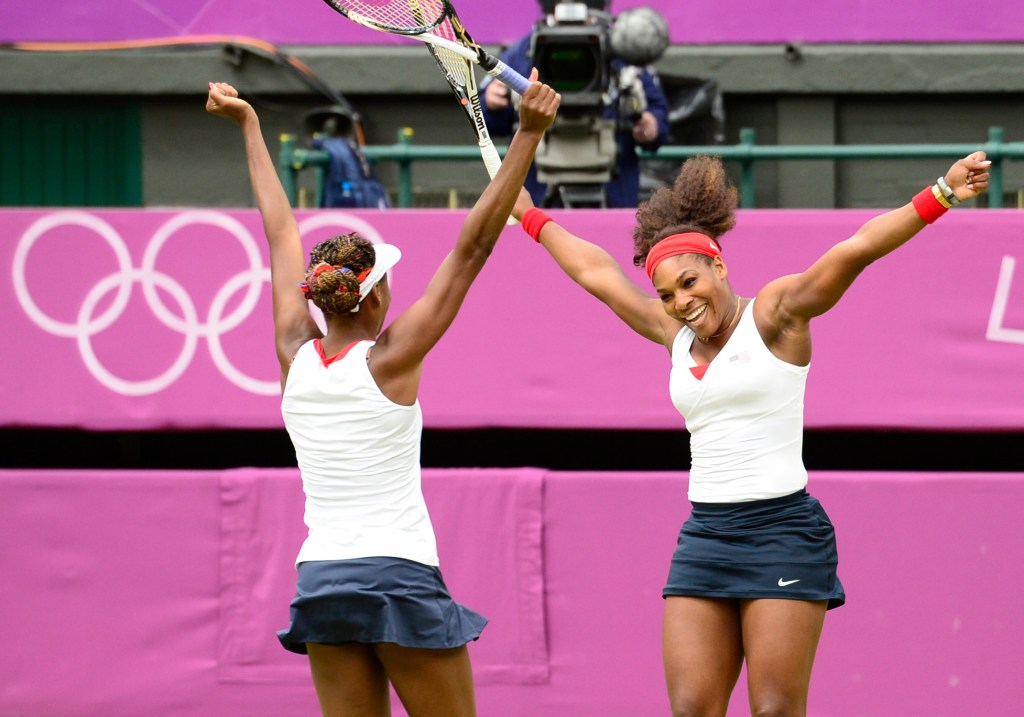 US Venus Williams (L) and Serena Williams celebrate after winning the women's doubles gold medal match of the London 2012 Olympic Games by defeating Czech Republic's Andrea Hlavackova and Lucie Hradecka, at the All England Tennis Club in Wimbledon, southwest London, on August 5, 2012. AFP PHOTO / LEON NEAL        (Photo credit should read LEON NEAL/AFP/GettyImages)
