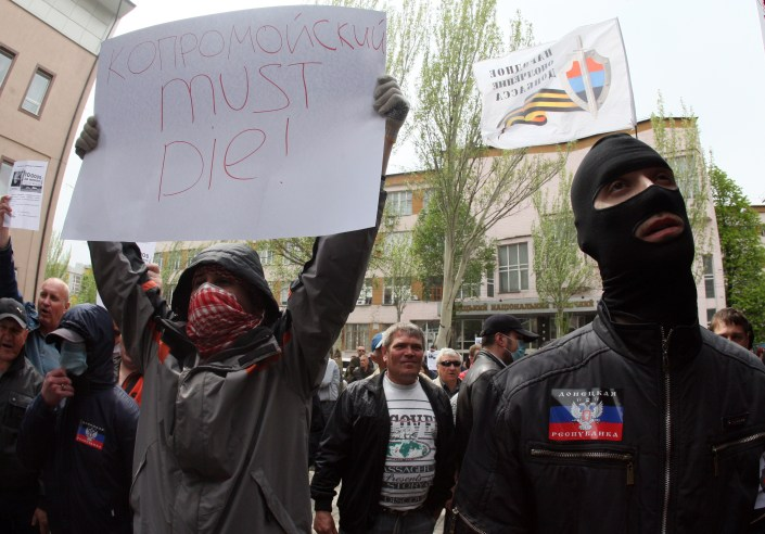 """A pro-Russian militiant holds placard reading """" Kolomoisky must die!"""" during the attack of a branch of Ukrainian bank Privatbank in the eastern Ukrainian city of Donetsk on April 28, 2014. Some 300 masked pro-Russian militants wielding baseball bats attacked a branch of the bank owned by an oligarch regional governor who has voiced criticism of Moscow. The gang attacked the Donetsk office of the powerful Private banking and metal industry holding belonging to Igor Kolomoisky, a billionaire who is also governor of the nearby region of Dnipropetrovsk. AFP PHOTO/ ALEXANDER KHUDOTEPLY (Photo credit should read Alexander KHUDOTEPLY/AFP/Getty Images)"""