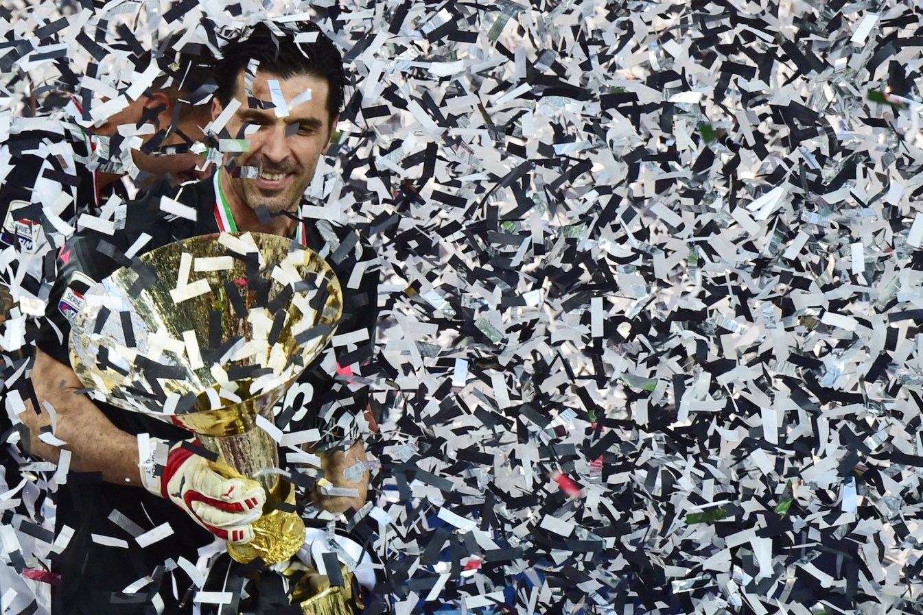 Juventus' goalkeeper and captain Gianluigi Buffon celebrates with the Italian League's trophy during a ceremony following the Italian Serie A football match Juventus vs Napoli on May 23, 2015 at the Juventus stadium in Turin. Juventus won the Coppa Italia on May 20, 2015 and the Italian League today after their 3-1 victory over Napoli. AFP PHOTO / GIUSEPPE CACACE (Photo credit should read GIUSEPPE CACACE/AFP/Getty Images)