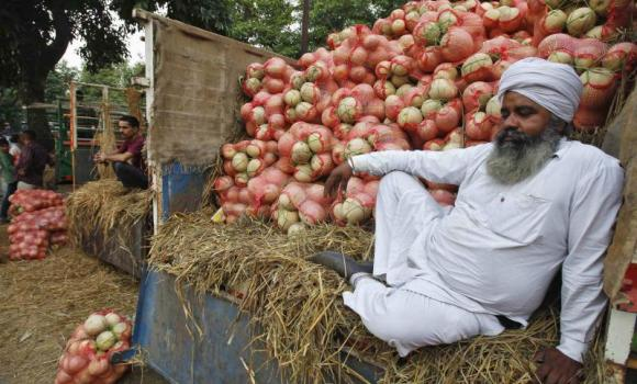 A farmer sits on a trolley loaded with melons as he waits for customers at a fruit and vegetable market in the northern city of Chandigarh. (Reuters)