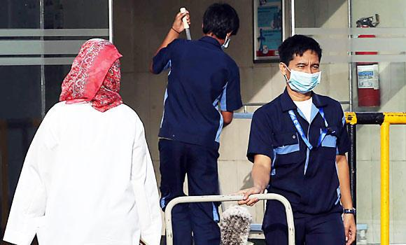 A hospital employee wear as mouth and nose mask as he leaves a local hospital's emergency department, in this April 22, 2014 photo, in the Red Sea coastal city of Jeddah.