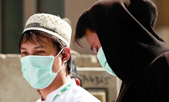 In this May 13, 2014 photo, Muslim pilgrims wear surgical masks to prevent infection from respiratory virus known as the Middle East respiratory syndrome (MERS) in the holy city of Mecca, Saudi Arabia. (AP)