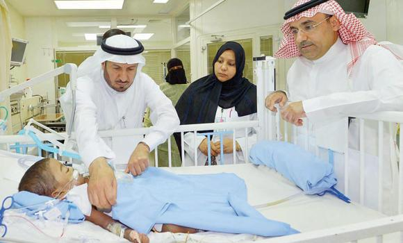 Dr. Abdullah Al-Rabeeah, left, checks one of the separated twins at the King Abdulaziz Medical City in Riyadh on Monday. At right is the chief medical officer of the hospital, Dr. Saad Al-Mahrij. (AN photo)