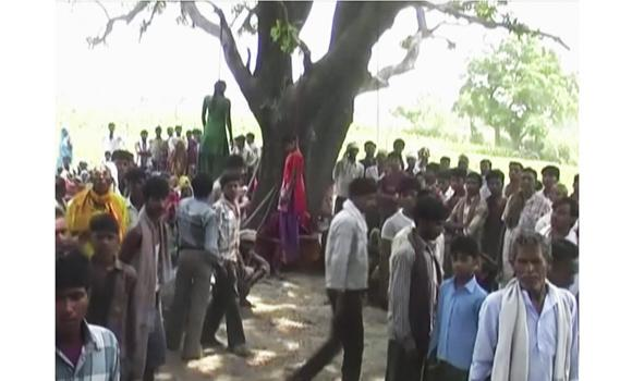 In this May 28, 2014 image taken from video, villagers gather around the bodies of two teenage sisters hanging from a tree in Katra village in Uttar Pradesh state, India.